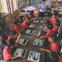High tech: Students use tablet computers at the Ban San Kong school in Mae Chan, northern Thailand, last month. | AFP-JIJI