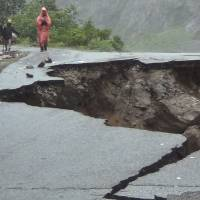 Dangerous path: Villagers examine a collapsed stretch of the Rishikesh-Mana highway on Monday after torrential rain wreaked havoc in the Indian state of Uttarakhand. | AP
