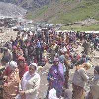 Wet and waiting: Pilgrims wait to be evacuated from Kedarnath in the northern Indian state of Uttrakhand on Thursday. Rescuers used helicopters and mountain paths to reach nearly 4,000 people trapped by landslides in a narrow valley near a Hindu shrine. | AP