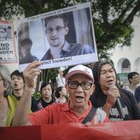 Rallying figure: Protesters shout slogans in support of former U.S. National Security Agency contractor Edward Snowden as they march to the U.S. Consulate in Hong Kong on June 13. | AFP-JIJI