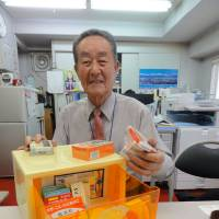 Medicine man: Masao Inoya, immediate past chairman of the Tokyo-to Iyakuhin Haichi Kyokai (Tokyo Metropolitan Medicine Placement Association), displays some of the medicines that stock an okigusuri medicine box.