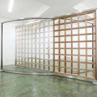'Wood Grid Crossing Two-way Mirror' (2010), which is among the works on show in Dan Graham's current exhibition at the Taka Ishii Gallery in Tokyo along with original photographs from his 'Homes for America' series begun in 1966. | DAN GRAHAM