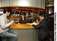Owner Hisae Iwakura chats with a drinker at 'stand bar' Buchi in Shinsen-cho (above); and a selection of sake at the bar