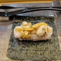 Rice topped with cooked tsubugai whelks, eaten in the style of te-maki (hand-rolled) sushi.