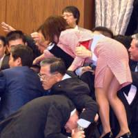 Fight club: Then opposition DPJ lawmaker Yuko Mori swarms toward the chairman on July 25, 2003, as she strives in vain to halt the passage of the ruling party's Upper House bill authorizing the dispatch of SDF forces to Iraq. | AP PHOTO