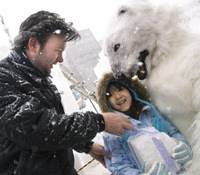 Kamiel Verschuren and Mami Odai (in a polar bear outfit) hand out a block of compacted snow to a young passerby during the Sapporo Snow Festival in Sapporo on Feb.5. (Below) A couple has their photo taken in front of a sculpture of well-known anime character Chibi Maruko-chan and her friends during the snow festival. | ROB GILHOOLY PHOTO