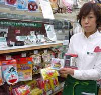 Hot tips: Yoshiko Sasaki, a staffer at the Tokyu Hands store in Shibuya, central Tokyo, displays a range of iron-filled and other body warmers from the shelves. | TOMOKO OTAKE PHOTO