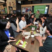 Trivia pursuit: People take part in a pub quiz organized by Oxfam Japan at the FooTNiK pub in Ebisu, Shibuya Ward, Tokyo, on Feb. 16. Participants pay 1,000, which goes to the international aid organization. | YOSHIAKI MIURA PHOTOS