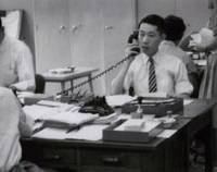 Action man: Yoshiharu Fukuhara (far left) takes the phone at Shiseido's head office in Tokyo's Ginza district shortly after he began working at the company in 1953. Left: Fukuhara in 1986 (right) with French designer Serge Lutens, who worked on Shiseido's branding for the European market in the 1980s. | SHISEIDO PHOTOS