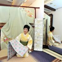 Sitting pretty: Hideko Kariya in her Hideya store in central Tokyo surrounded by some of the many beautiful garments she sells, both of the traditional variety and others using Velcro fastenings to significantly speed up the long business of getting attired. | YOSHIAKI MIURA PHOTOS