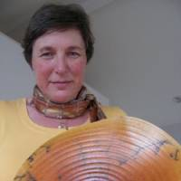 Swanica Ligtenberg holds a plate titled 'Circles of Life' at her studio in Kamakura, Kanagawa Prefecture. Below is one of her ceramic works ? a tea bowl featuring wave patterns. | ANGELA JEFFS, COURTESY OF SWANICA LIGTENBERG