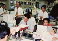 On deadline: Renho (seated on the right) reads a script before she goes live on air during her early 1990s stint as an anchorwoman for 'Station Eye,' a TV Asahi news program. | COURTESY OF RENHO