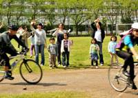 Rousing sendoff: Hearing-impaired students at Meisei Gakuen and their parents wave to the cyclists Friday before they set out to Osaka.