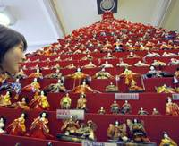 All dolled up: A girl looks at hina dolls lined up on terraced shelves at Konosu City Hall, Saitama Prefecture, in 2008. The dolls, clad in ancient court costume, are believed to protect girls from evil. | AP PHOTO