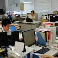'Deals get made': Masa Sugano, director for Africa in the Trade Policy Bureau at the Ministry of Economy, Trade and Industry, works behind his spartan desk in METI's Middle East and Africa Division.   DREUX RICHARD