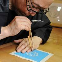 Hatoba at work on one of his detailed family-crest designs. | SATOKO KAWASAKI PHOTO