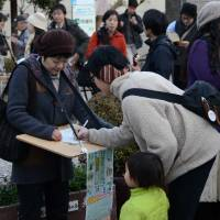 My way or the highway: Activists gather 'signatures' in December for a petition calling for a referendum on the planned road through Kodaira Chuo Park. | KAROKU KATO