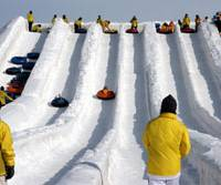 Snow patrol: Kids use inner-tubes to rocket down a snow slide at last year's annual Sapporo Snow Festival in Hokkaido.