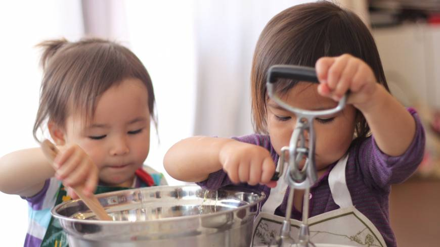 Baking friends: Two of the young cooks get to grips with stirring ingredients into the cake mix.