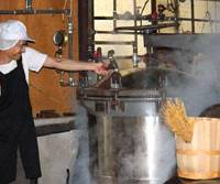 Kiyoshi's son-in-law, Yutaka Watanabe, lets off steam from the pressure cooker when the beans are at their best.