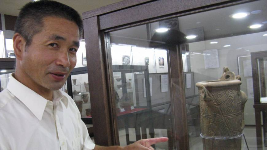 Idojiri Archaeological Museum director Seishi Higuchi (right) points to one of his star finds from the Jomon era.