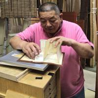Motonobu Murayama, whose Yamayasu company supplies the materials for tea houses and also constructs them, open an archived 3-D paper scale model of one of their creations.   KIT NAGAMURA PHOTO