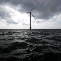 Breezing up: A 2.4-megawatt wind turbine developed by New Energy and Industrial Technology Development Organization and Tokyo Electric Power Co. stands off Choshi, Chiba Prefecture, in March. A Marubeni Corp.-led group will set up a floating wind farm off Fukushima this month. | BLOOMBERG