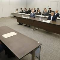 One's a crowd: A Finance Ministry official attends a Thursday general shareholders' meeting of Japan Post Holdings Co. in Tokyo's Kasumigaseki district. | KYODO
