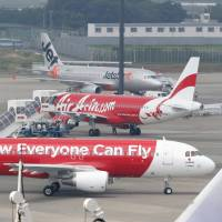 Crosscheck: A pair of AirAsia Japan jetliners sit on the tarmac at Narita International Airport last July. | KYODO