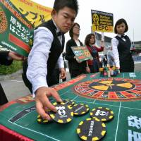 Outside bet: Members of environmental group Greenpeace display a roulette board likening nuclear energy to gambling, while investors walk to Tokyo Electric Power Co's shareholders' meeting in Tokyo on Wednesday. | AFP-JIJI