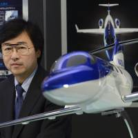 Approaching takeoff speed: Michimasa Fujino, president of Honda Aircraft Co., poses Wednesday by a model of the firm's business jet. | BLOOMBERG