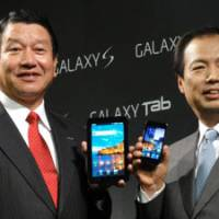 Into the galaxy: DoCoMo President Ryuji Yamada (left) and J.K. Shin, president and head of the mobile communications business at Samsung, show off the new Galaxy Tab and the Galaxy S smart phone at a press conference Tuesday. | KAZUAKI NAGATA PHOTO