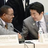Safe and sound: Prime Minister Shinzo Abe greets Ethiopian Prime Minister Hailemariam Desalegn at a symposium on human security Sunday in Yokohama on the sidelines of the Tokyo International Conference on African Development. | AP