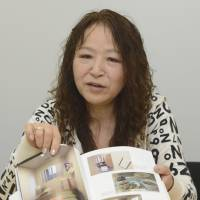 Inside stories: Photographer Hitomi Toyama shows her recently published book of photos of life at prisons across Japan on April 3 in Tokyo. | KYODO