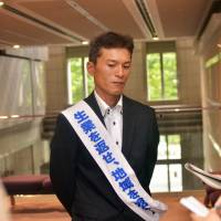 Seeking justice: Kazuya Tarukawa, whose father hanged himself after authorities banned shipments of farm produce from Fukushima because of fears it was contaminated by radiation in 2011, faces reporters Thursday in Tokyo. | AFP-JIJI