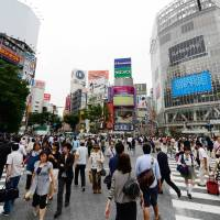 By the numbers: People cross the busy intersection in front of JR Shibuya Station on June 6. In 2015, residents of Japan, including foreigners, will each be assigned an ID number whose use will start in 2016. | AFP-JIJI