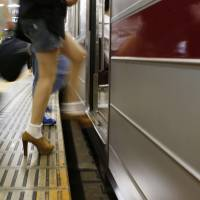 Through the gap: A passenger boards the Hibiya Line on Monday at Tokyo's Roppongi Station, where a woman slipped through the gap between the platform and a train the previous day. | KYODO