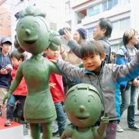 A taxing woman: A child poses with bronze statues of Sazae-san (left) and her son, Tara-chan, in the Sakurashinmachi shopping district in Tokyo's Setagaya Ward in March 2012. | KYODO