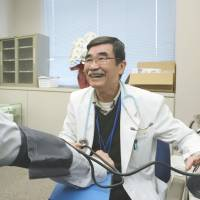 Service with a smile: Dr. Shunji Sekine measures the blood pressure of a local official May 9 at a temporary clinic in the town of Namie, Fukushima Prefecture. | KYODO