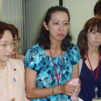 Speaking out: Mika Matsufuji (center), who represents a parents' association of cervical cancer vaccination victims, answers reporters' questions Friday at the health ministry in Tokyo. | KYODO