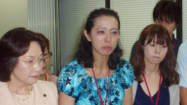 Speaking out: Mika Matsufuji (center), who represents a parents' association of cervical cancer vaccination victims, answers reporters' questions Friday at the health ministry in Tokyo.