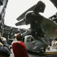 Packed up: An MV-22 Osprey is taken below deck after landing on the Japanese destroyer Hyuga off San Diego on Friday. | KYODO