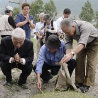 Staying in touch: Japanese whose relatives perished in North Korea after the end of World War II offer prayers Sunday during a visit to the site near the port of Chongjin, which the North says holds the remains of some 3,300 Japanese who died at a Soviet prison that stood there. | KYODO