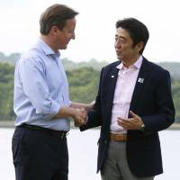 Let's talk: British Prime Minister David Cameron, who is hosting the Group of Eight summit, greets Prime Minister Shinzo Abe in Enniskillen, Northern Ireland, on Monday. | KYODO