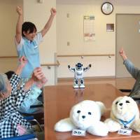 High hopes: Residents of the Fuyouen senior home interact with tiny robot Palro and two Paro therapy bots in Yokohama on May 10. | KYODO