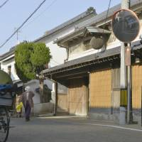 Revival push: A man bicycles past old homes in the Tsuyazaki district of Fukutsu, Fukuoka Prefecture, in April. | KYODO