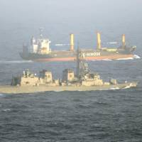 Anti-piracy patrol: A Maritime Self-Defense Force vessel (front) sails close to a Japanese commercial vessel heading through the Gulf of Aden off Somalia in June 2009. | KYODO