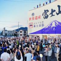 Huzzah!: Residents of Fujiyoshida, Yamanashi Prefecture, at the foot of Mount Fuji celebrate UNESCO's decision to register the peak as a World Heritage site Saturday in front of City Hall, whose wall bears a huge sign reading 'World Heritage Fuji-san, City of Hospitality Fujiyoshida.' | KYODO