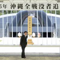 Remembering those lost: Prime Minister Shinzo Abe offers a floral tribute Sunday at the ceremony for the 68th anniversary of the end of the Battle of Okinawa. | KYODO