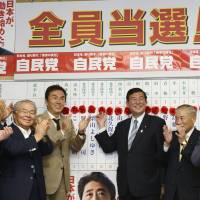 Painting the town red: Liberal Democratic Party Secretary General Shigeru Ishiba (center right) and other Diet members celebrate election tallies in Tokyo on Sunday night. | KYODO